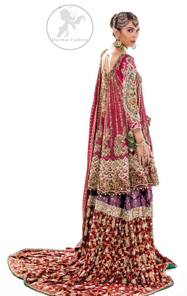 This bridal dress is adorned with floral embroidery.It is meticulously highlighted with dull golden and antique shaded kora, dabka, tilla, sequins and pearls. It has beautiful embellished bodice and U-shaped neckline which adds to the look.Sleeves are embellished with embroidered applique. Hemline is adorned with beautiful tassels. It is artistically coordinated with brocade embellished gharara. Gharara is allured with beautiful contrast of rust and plum color. It comes with pink dupatta which is decorated with embroidered borders and sprinkled sequins all over.