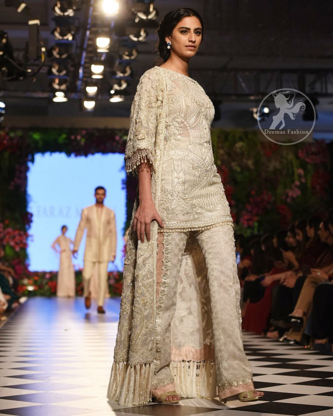 Go for this trendy dress. This dress is heavily embellished with floral and geometric styled embroidery decorated with silver kora, dabka, swarovski and pearls. Gown is enhanced with scalloped border decorated with thread clusters finishing. Third quarter sleeves are embellished with floral motifs all over along with tassels at the end. Trousers is magnificently decorated with cutwork. It is coordinated with tissue dupatta which is sprinkled with sequins all over it.